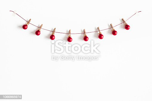 1074095098 istock photo Christmas composition. Garland made of red balls on white background. Christmas, winter, new year concept. Flat lay, top view, copy space 1066865974