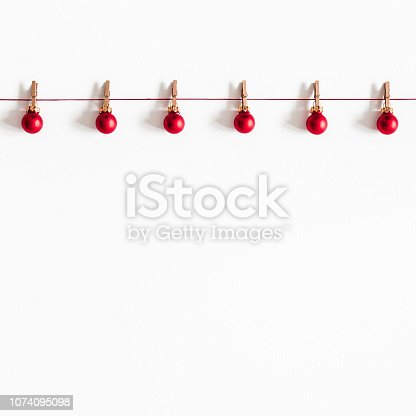 istock Christmas composition. Garland made of red balls on white background. Christmas, winter, new year concept. Flat lay, top view, copy space, square 1074095098