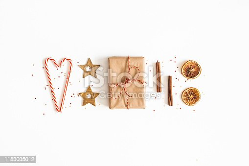 1076055746 istock photo Christmas composition. Gift box, candy canes, golden decorations on white background. Christmas, winter, new year concept. Flat lay, top view 1183035012