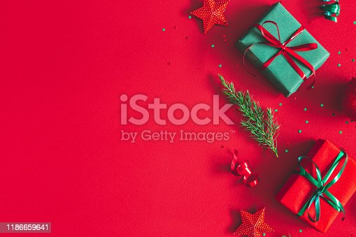 1062680370 istock photo Christmas composition. Gift box, christmas decorations on red background. Flat lay, top view, copy space 1186659641