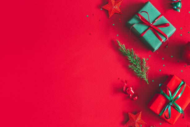 Christmas composition. Gift box, christmas decorations on red background. Flat lay, top view, copy space stock photo