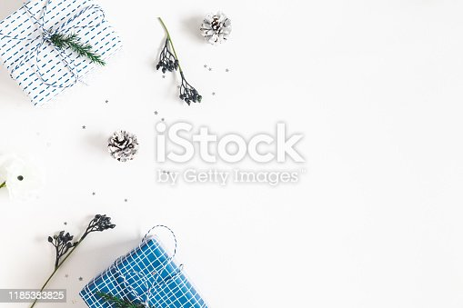 1076055746 istock photo Christmas composition. Gift box, fir tree branches, decorations on white background. Christmas, winter, new year concept. Flat lay, top view, copy space 1185383825