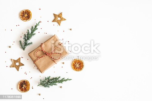 1076055746 istock photo Christmas composition. Gift box, fir tree branches, golden decorations on white background. Christmas, winter, new year concept. Flat lay, top view, copy space 1178051590
