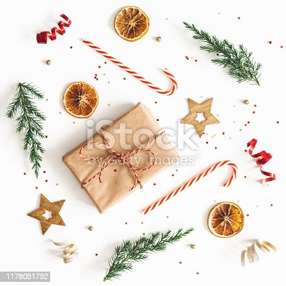 1076055746 istock photo Christmas composition. Gift box, fir tree branches, golden decorations on white background. Christmas, winter, new year concept. Flat lay, top view, square 1178051752