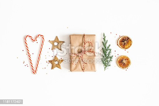 1076055746 istock photo Christmas composition. Gift box, fir tree branches, golden decorations on white background. Christmas, winter, new year concept. Flat lay, top view 1181172401
