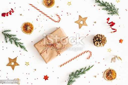 1076055746 istock photo Christmas composition. Gift box, fir tree branches, golden decorations on white background. Christmas, winter, new year concept. Flat lay, top view 1183894318
