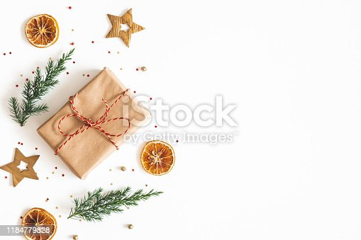 1076055746 istock photo Christmas composition. Gift box, fir tree branches, golden decorations on white background. Christmas, winter, new year concept. Flat lay, top view, copy space 1184779828