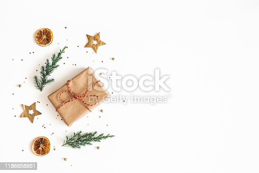 1076055746 istock photo Christmas composition. Gift box, fir tree branches, golden decorations on white background. Christmas, winter, new year concept. Flat lay, top view, copy space 1186658951