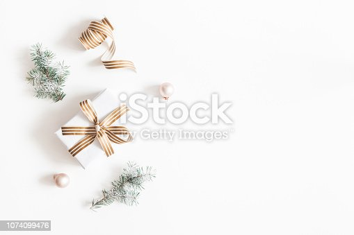 1060169304 istock photo Christmas composition. Gift, fir tree branches, balls on white background. Christmas, winter, new year concept. Flat lay, top view, copy space 1074099476