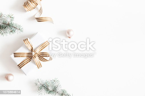 1060169304 istock photo Christmas composition. Gift, fir tree branches, balls on white background. Christmas, winter, new year concept. Flat lay, top view, copy space 1075884614