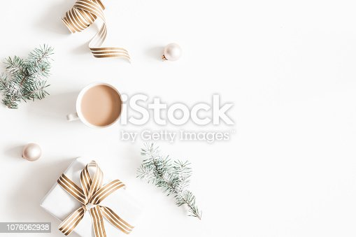 1060169304 istock photo Christmas composition. Gift, fir tree branches, cup of coffee, balls on white background. Christmas, winter, new year concept. Flat lay, top view, copy space 1076062938