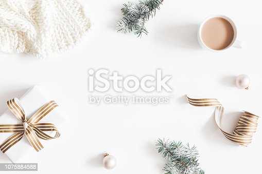 1060169304 istock photo Christmas composition. Gift, fir tree branches, plaid, cup of coffee, balls on white background. Christmas, winter, new year concept. Flat lay, top view, copy space 1075884588