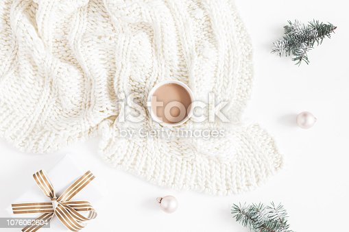 1060169304 istock photo Christmas composition. Gift, fir tree branches, plaid, cup of coffee, balls on white background. Christmas, winter, new year concept. Flat lay, top view 1076062604