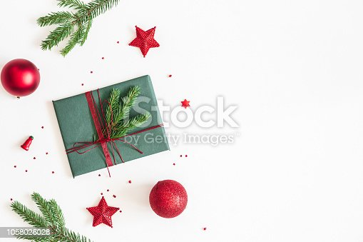 1060169304 istock photo Christmas composition. Gift, fir tree branches, red decorations on white background. Christmas, winter, new year concept. Flat lay, top view, copy space 1058026028
