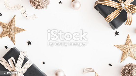 1060169304 istock photo Christmas composition. Gifts, black and golden decorations on white background. Christmas, winter, new year concept. Flat lay, top view, copy space 1076058196