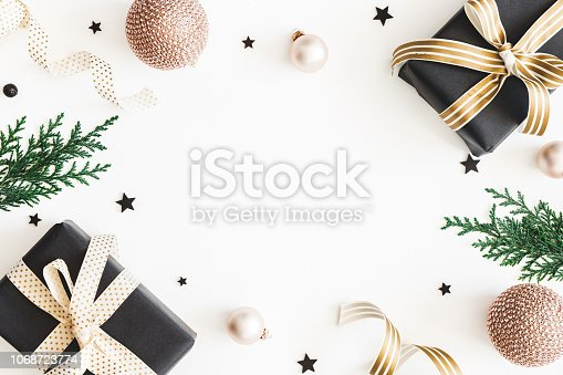 1060169304 istock photo Christmas composition. Gifts, fir tree branches, black and golden decorations on white background. Christmas, winter, new year concept. Flat lay, top view, copy space 1068723774