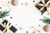istock Christmas composition. Gifts, fir tree branches, black and golden decorations on white background. Christmas, winter, new year concept. Flat lay, top view, copy space 1068723774