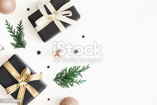 1060169304 istock photo Christmas composition. Gifts, fir tree branches, black and golden decorations on white background. Christmas, winter, new year concept. Flat lay, top view, copy space 1071430652
