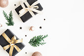 istock Christmas composition. Gifts, fir tree branches, black and golden decorations on white background. Christmas, winter, new year concept. Flat lay, top view, copy space 1071430652