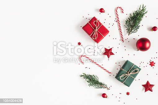 1060169304 istock photo Christmas composition. Gifts, fir tree branches, red decorations on white background. Christmas, winter, new year concept. Flat lay, top view, copy space 1054004426