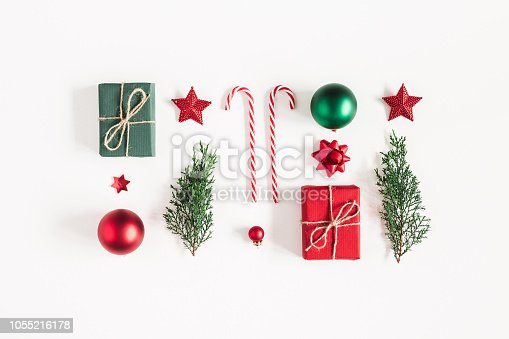 1062679964 istock photo Christmas composition. Gifts, fir tree branches, red decorations on white background. Christmas, winter, new year concept. Flat lay, top view, copy space 1055216178