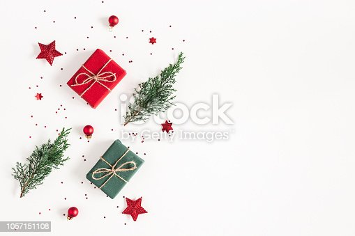 1062679964 istock photo Christmas composition. Gifts, fir tree branches, red decorations on white background. Christmas, winter, new year concept. Flat lay, top view, copy space 1057151108
