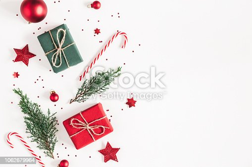 1060169304 istock photo Christmas composition. Gifts, fir tree branches, red decorations on white background. Christmas, winter, new year concept. Flat lay, top view, copy space 1062679964