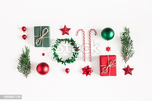 1062679964 istock photo Christmas composition. Gifts, fir tree branches, red decorations on white background. Christmas, winter, new year concept. Flat lay, top view 1065697230
