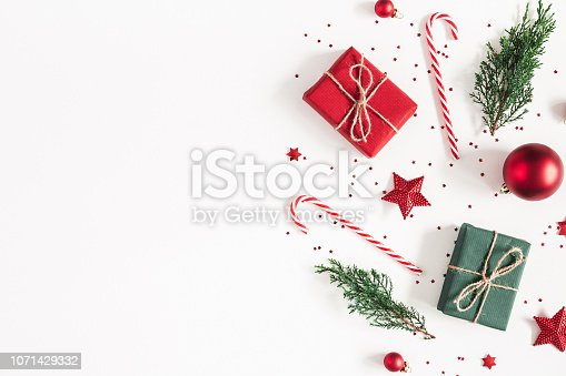 1060169304 istock photo Christmas composition. Gifts, fir tree branches, red decorations on white background. Christmas, winter, new year concept. Flat lay, top view, copy space 1071429332