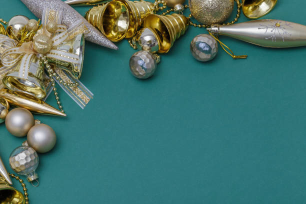 Christmas composition. Gifts, tree branches, golden and silver decorations on green background. Christmas, winter, new year concept. Flat lay, top view, copy space. stock photo