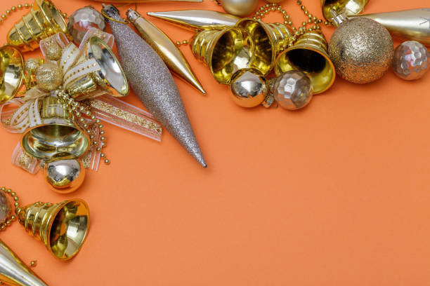 Christmas composition. Gifts, tree branches, golden and silver decorations on orange background. Christmas, winter, new year concept. Flat lay, top view, copy space. stock photo