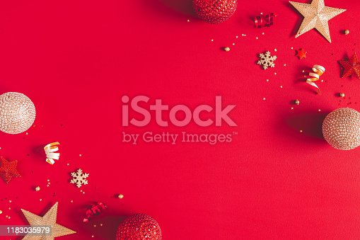 1062680370 istock photo Christmas composition. Golden and red decorations on red background. Christmas, winter, new year concept. Flat lay, top view, copy space 1183035979
