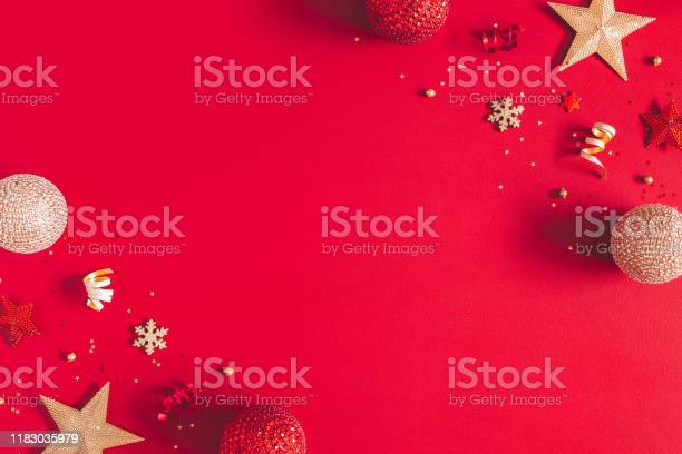Photo of Christmas composition. Golden and red decorations on red background. Christmas, winter, new year concept. Flat lay, top view, copy space