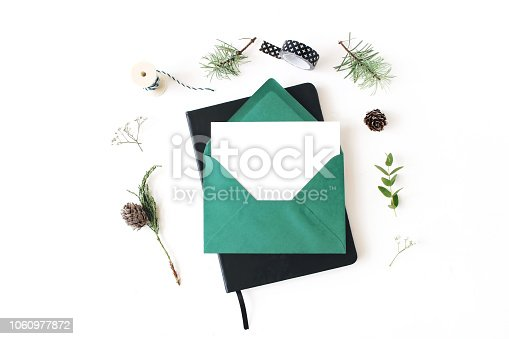 istock Christmas composition. Greeting card, envelope and note pad mock-up scene. Frame of pine, eucalyptus and juniperus tree branches, pine cones and baby breath flowers. White table background. Flat lay. 1060977872