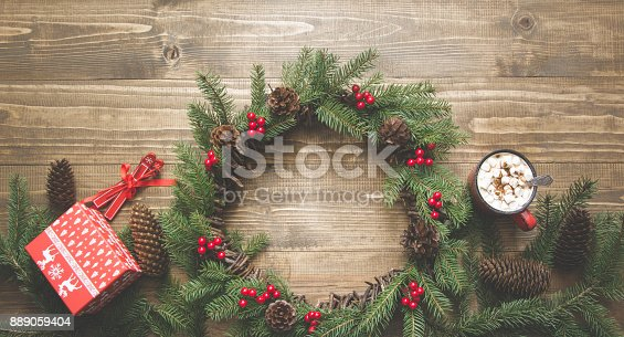 istock Christmas composition of floral wreath , gift boxes, red decor on wooden board. Flat lay. Top view. Copy space. 889059404