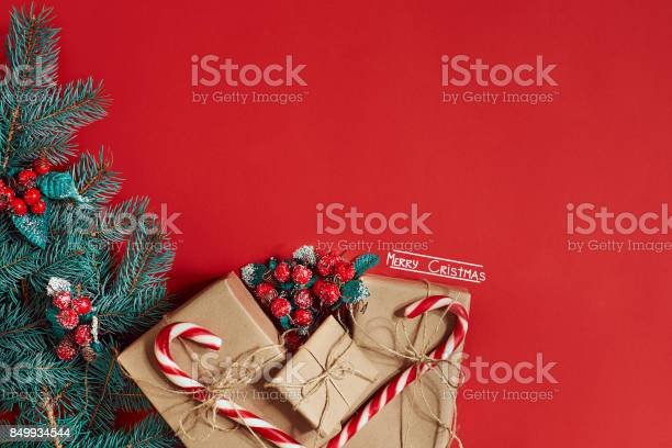 Photo of Christmas composition of pine cones, spruce branches and stack of gift boxes on red background