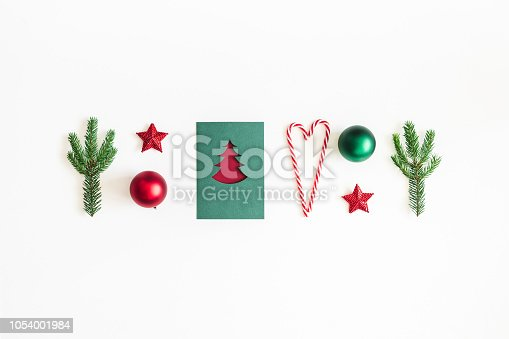 1064023690 istock photo Christmas composition. Postcard, fir tree branches, red and green decorations on white background. Christmas, winter, new year concept. Flat lay, top view 1054001984