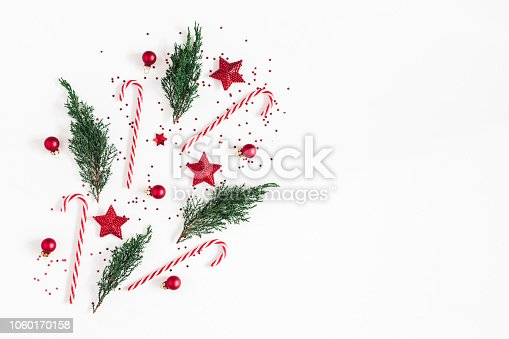 1062679964 istock photo Christmas composition. Red decorations, fir tree branches on white background. Christmas, winter, new year concept. Flat lay, top view, copy space 1060170158