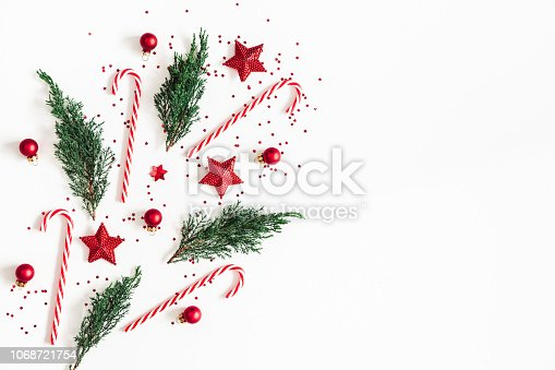 1076057502 istock photo Christmas composition. Red decorations, fir tree branches on white background. Christmas, winter, new year concept. Flat lay, top view, copy space 1068721754