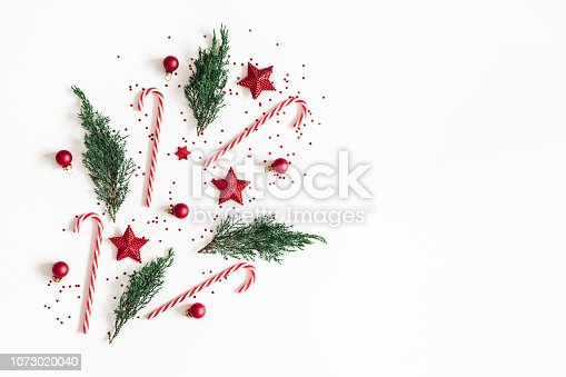 1062679964 istock photo Christmas composition. Red decorations, fir tree branches on white background. Christmas, winter, new year concept. Flat lay, top view, copy space 1073020040