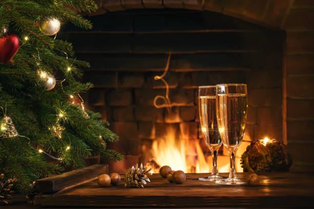 Weihnachtskomposition - Zwei Gläser mit Champagner auf einem Holztisch in der Nähe eines Weihnachtsbaumes in einem Zimmer mit brennendem Kamin – Foto