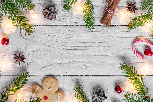 istock Christmas composition with christmas lights, food, fir tree, berries and pine cones on white wooden background 1074884672