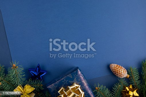 istock Christmas composition with decorations, gift boxes baubles and branches of fir tree on classic blue background 1192588800