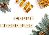 istock Christmas composition with fir tree branches, christmas tree cones and gift on white. Text Merry Christmas 1276649474