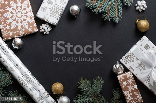 Christmas composition with gift boxes, paper's rools and decorations on black background. Preparation for holidays concept. Flat lay, top view, overhead