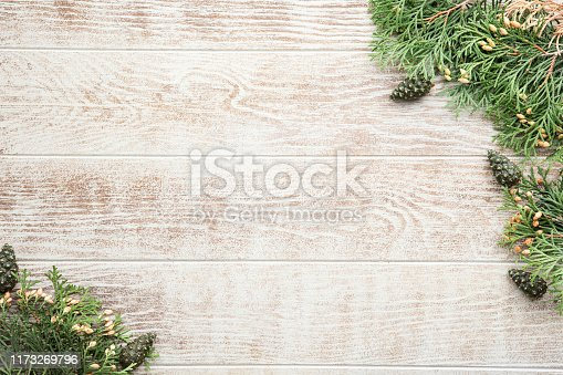 istock Christmas composition with pine cones, fir branches on wooden beige background. Flat lay, top view 1173269796