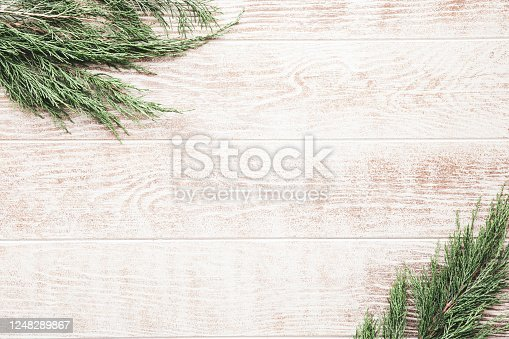 Christmas composition with pine cones, fir branches on wooden beige background. Flat lay, top view