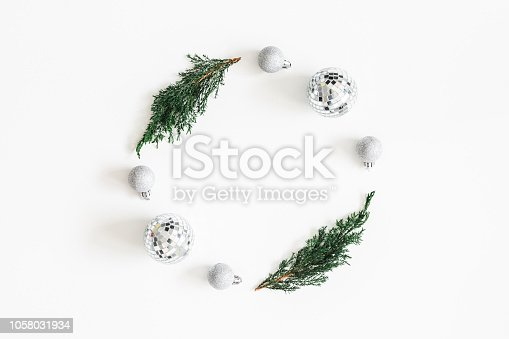 istock Christmas composition. Wreath made of fir tree branches, disco balls on white background. Christmas, winter, new year concept. Flat lay, top view, copy space 1058031934