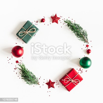 1060169304 istock photo Christmas composition. Wreath made of gifts, fir tree branches, red decorations on white background. Christmas, winter, new year concept. Flat lay, top view, copy space, square 1076055746