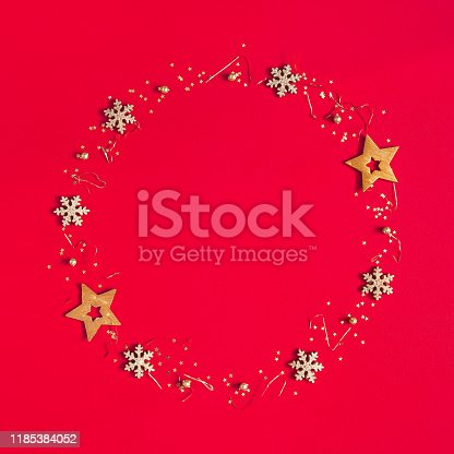 1062680370 istock photo Christmas composition. Wreath made of golden decorations on red background. Christmas, winter, new year concept. Flat lay, top view, copy space 1185384052